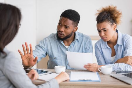 Foto de Angry afro couple criticizing and rejecting insurance brokers advice sitting at her office. Selective focus - Imagen libre de derechos