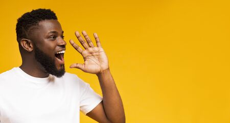 Photo pour Attractive african guy shouting at copy space, making announcement, sharing news on yellow studio background. Panorama - image libre de droit