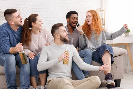 Photo for Happy friends singing karaoke, having fun and spending time together at home - Royalty Free Image