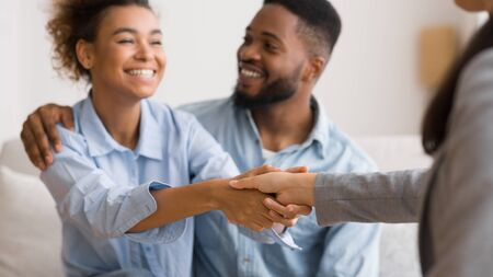 Photo pour Effective Marital Therapy. Thankful Afro Spouses Handshaking With Relationship Coach In Office. Selective Focus, Panorama - image libre de droit
