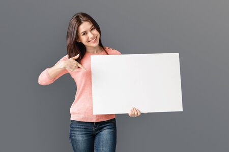 Photo for Young Caucasian Woman Holding White Blank Card, pointing at blank - Royalty Free Image