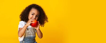 Photo pour Cute afro girl biting red apple and looking at camera over yellow background, free space - image libre de droit