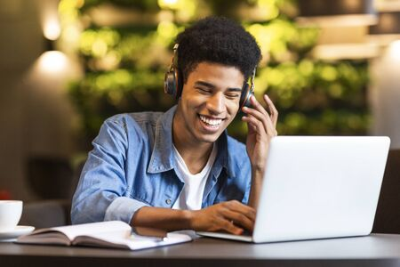 Photo pour Cheerful black young guy with headset looking at laptop, having fun while studying, cafe interior - image libre de droit