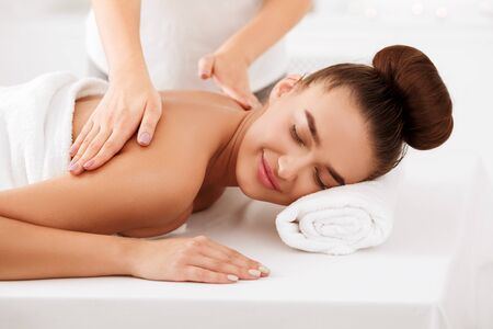 Photo pour Relaxed girl enjoying back massage in spa salon, resting with closed eyes - image libre de droit