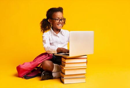 Photo pour Cheerful African American Schoolgirl Sitting At Laptop Doing Homework Over Yellow Background In Studio. - image libre de droit