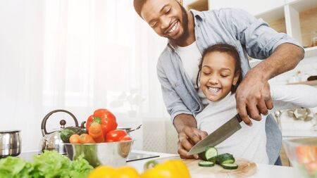 Foto de Cooking together. African father and daughter cutting cucumber together, making salad, kitchen interior, copy space - Imagen libre de derechos