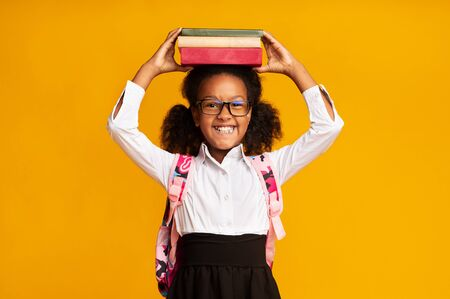 Foto per Cute Black Schoolgirl Holding Books On Head Over Yellow Background. Back To School Concept, Studio Shot - Immagine Royalty Free