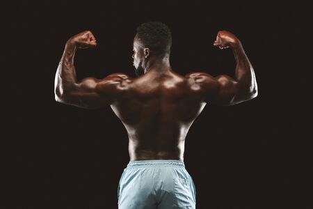 Photo for Muscular Athletic African Bodybuilder Fitness Model Posing After Exercises, back view over black studio background - Royalty Free Image
