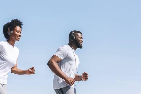Foto de Happy African American Couple Jogging Together Outdoor. Sport And Healthy Lifestyle. Copy Space - Imagen libre de derechos