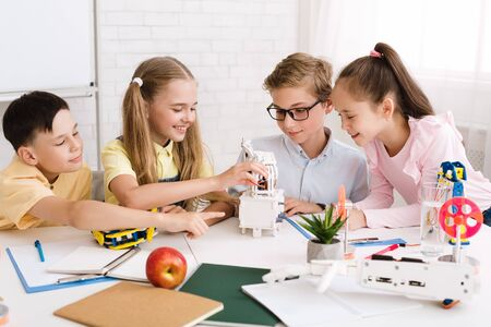 Photo pour Happy children creating robots at stem class, working together in group - image libre de droit