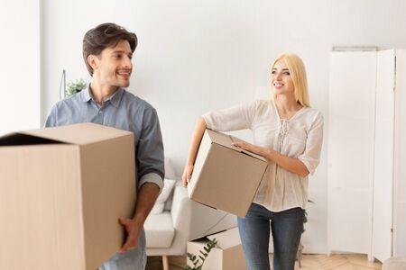 Photo pour Moving House. Happy Couple Carrying Packed Boxes Entering New Home. Selective Focus - image libre de droit