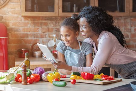 Photo pour Happy parenthood. Black woman and her cute daughter reading recipe on tablet, cooking at kitchen, copy space - image libre de droit