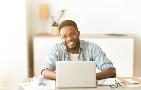 Photo pour Positive african american freelancer posing to camera and laughing - image libre de droit
