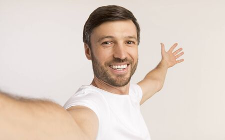 Photo for Look At This. Smiling Man Taking Selfie Gesturing With Hands Showing Something Behind Him On White Studio Background. Isolated - Royalty Free Image