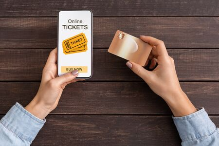 Photo for Woman buying event tickets via app on smartphone and credit card, dark wooden background - Royalty Free Image