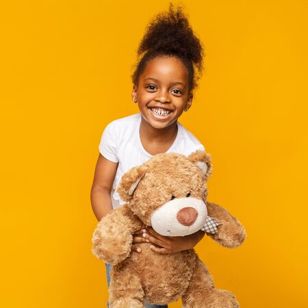 Photo pour Favorite toy. Cute african baby girl laughing with her teddy bear, yellow studio background - image libre de droit