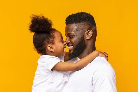 Foto de Tender moments of fatherhood. African daddy and his little daughter touching noses, orange studio background - Imagen libre de derechos