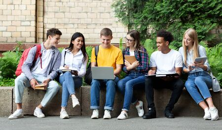 Photo for Education concept. Happy teens preparing for exams in university campus with books and laptop - Royalty Free Image