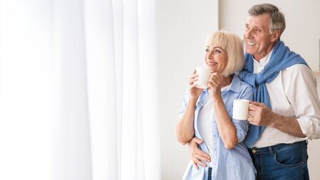 Photo pour Happy senior couple drinking tea near window and embracing, free space - image libre de droit