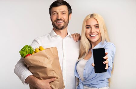 Photo pour Online Grocery. Happy Couple Showing Empty Cellphone Screen Holding Shopping Bag With Vegetables On White Background In Studio. Mockup - image libre de droit