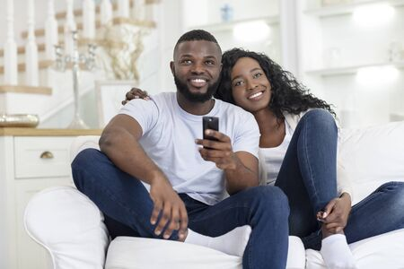 Foto de Happy Millennial Couple Embracing And Watching TV, Sitting On Sofa In Living Room - Imagen libre de derechos