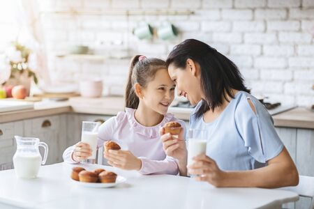 Photo pour Mother and daughter eating cupcakes and drinking milk, spending time together in kitchen. - image libre de droit