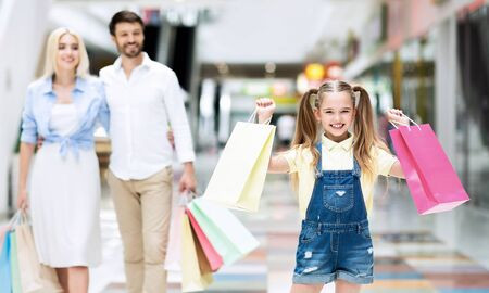 Photo pour Young Parents And Excited Little Daughter Carrying Shopping Bags Walking Together In Mall Buying Seasonal Updates. Selective Focus - image libre de droit