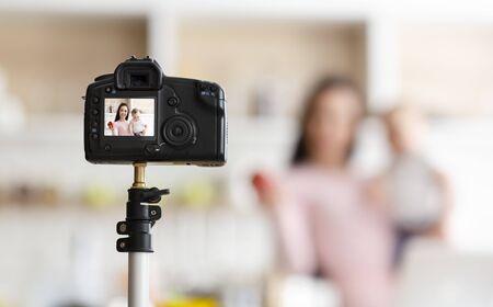 Photo pour Baby nutrition online courses. Mother with toddler recording video for webinar, kitchen interior, empty space - image libre de droit