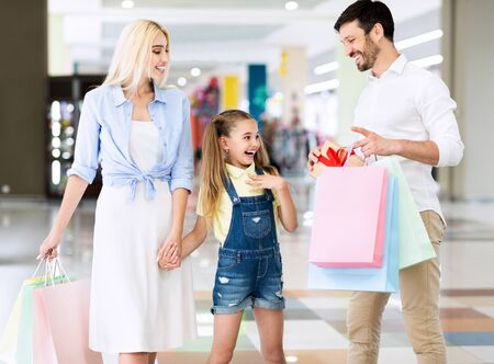 Photo pour Parents Giving Daughter A Gift During Shopping In Hypermarket. Mall Birthday Surprise And Discounts. - image libre de droit
