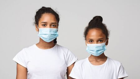 Photo pour Virus and flu concept. Two young african sisters wearing medical masks over grey studio background, panorama - image libre de droit