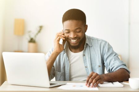 Photo for Great news. Portrait of cheerful african american businessman talking on phone and reading documentation at workplace - Royalty Free Image