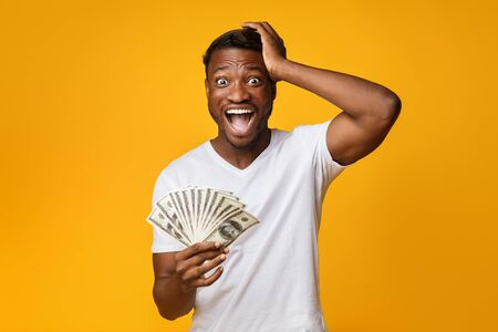 Foto für Excited Afro Guy Holding Money Shouting Touching Head Standing On Yellow Studio Background. Big Luck. Free Space - Lizenzfreies Bild