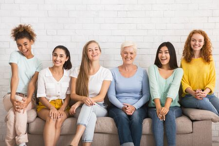 Photo pour Smiling Diverse Women Looking At Camera Sitting On Sofa Over White Brick Wall Indoor. Togetherness Concept - image libre de droit