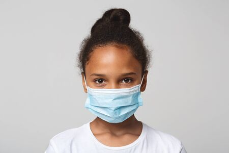 Foto de Infection concept. Portrait of little african american girl wearing medical mask, grey background - Imagen libre de derechos