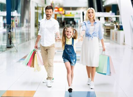 Family Walking Together In Shopping Mall Holding Hands And Smiling At Camera. Seasonal Sales