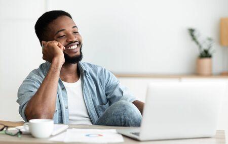 Foto de Handsome black man talking on phone while sitting at workplace in office - Imagen libre de derechos