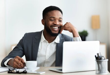 Photo pour Portrait of cheerful african american employee sitting at workplace in modern office, drinking coffee. Copy space - image libre de droit