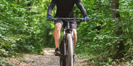 Photo for Sport equipment and clothes. Male cyclist riding bike among trees, free space - Royalty Free Image