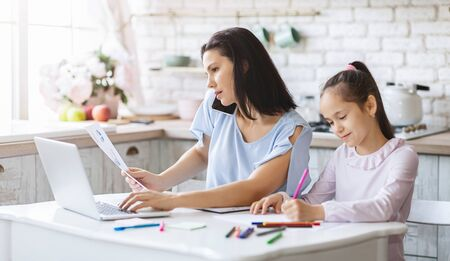 Photo for Busy family. Mother working from home while daughter doing her homework in kitchen, panorama - Royalty Free Image