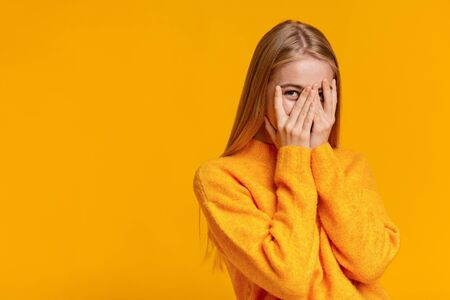 Photo pour Shy teenage girl peeking through fingers, covering face with both hands over orange studio background with copy space - image libre de droit
