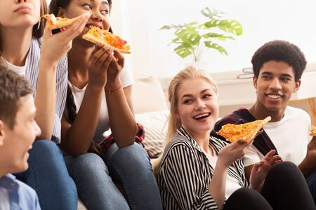 Photo pour Pizza time. Diverse friends eating and talking, spending time together at home - image libre de droit