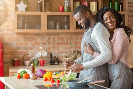 Foto de Grateful african american wife embracing her husband from behind at kitchen, making dinner together, copy space - Imagen libre de derechos