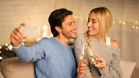 Foto de Young couple celebrating anniversary with champagne at home and making selfie on phone - Imagen libre de derechos