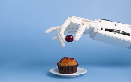 Photo pour Kitchen robotization. Robot hand putting fresh cherry on top of the cupcake, blue background - image libre de droit