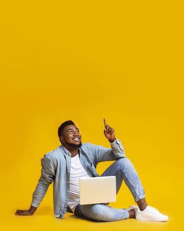 Photo pour Great offer. Black millennial guy sitting on floor with laptop and pointing upwards at copy space on yellow - image libre de droit