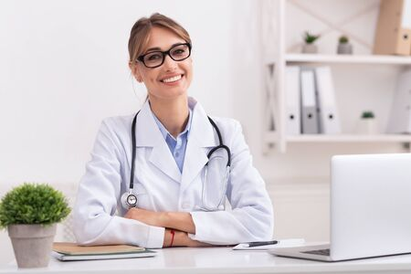 Photo pour Family Medical Doctor. Positive Woman Physician Smiling Looking At Camera Sitting In Her Office. - image libre de droit