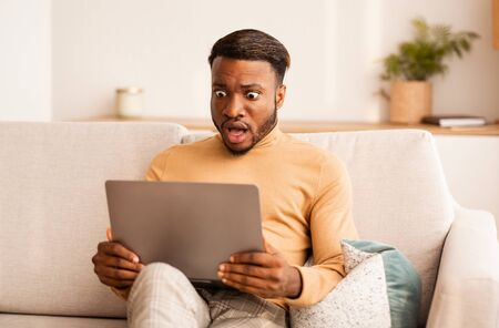 Foto für Shocked Black Guy Looking At Laptop Computer Working Sitting On Couch At Home. Selective Focus - Lizenzfreies Bild