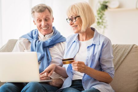 Photo for E-Commerce. Mature couple using laptop and credit card, buying things on Internet - Royalty Free Image