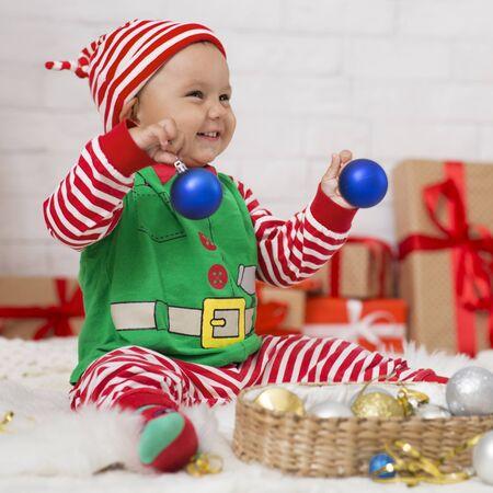 Foto de Xmas tradition. Happy baby enjoying Christmas home decoration, playing with blue balls - Imagen libre de derechos