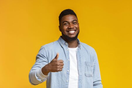 Photo pour Right choice. Portrait of smiling blach guy showing thumb up at camera over yellow background with free space - image libre de droit